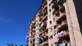 Secado de la ropa en una cuerda para tender la ropa entre los balcones en la casa vieja de gran altura en un área pobre de la ciu metrajes