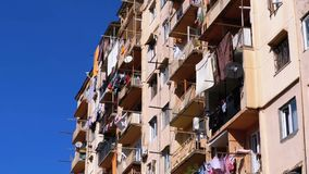 Secado de la ropa en una cuerda para tender la ropa entre los balcones en la casa vieja de gran altura en un área pobre de la ciu almacen de video