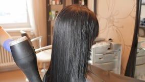 Secado del pelo El enderezarse de la queratina y restauración del pelo Consolidación y tratamiento con el botox almacen de metraje de vídeo