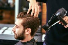 Secado, diseñando el pelo de los hombres en un salón de belleza Foto de archivo libre de regalías