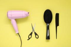 Secador de pelo, cepillo, peine y tijeras en fondo de papel amarillo Imagen de archivo