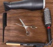 Secador de pelo, hierro que se encrespa, peine y tijeras en el pelo marrón Imágenes de archivo libres de regalías