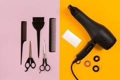Secador, peine y tijeras de pelo negro en fondo de papel rosado y amarillo Visión superior fotos de archivo