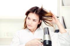 Secagem da menina seu cabelo em casa Imagens de Stock Royalty Free