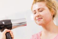 A secagem da mulher sua descasca fora o secador de cabelo da máscara protetora fotografia de stock royalty free