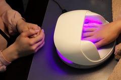 Secar e fixar uma base da base transparente aplicaram-se aos pregos antes de usar a goma-laca com uma lâmpada ultravioleta fotografia de stock