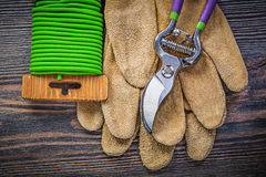 Secateurs leather protective gloves soft twist tie on wooden boa. Rd gardening concept Stock Image