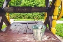 Secchio accovacciato di acqua che sta sul pozzo di legno dello scaffale Immagini Stock Libere da Diritti