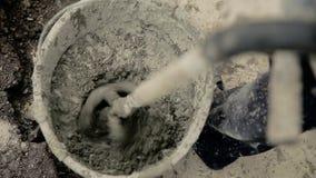 Secchio con il mortaio grigio che si mescola e che si mescola per lavorare stock footage