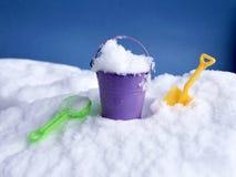 Secchio del giocattolo con neve e pale su neve su un fondo blu fotografia stock