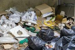Secchio della spazzatura con schiuma, cassa di carta, borsa di immondizia nera, vecchie scarpe Fotografia Stock
