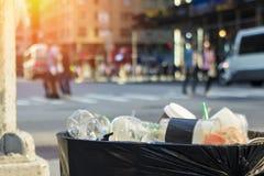 Secchio della spazzatura dei rifiuti sulla via di New York City con la gente Immagine Stock