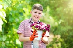 Secchio della tenuta del ragazzo con i fiori fotografie stock libere da diritti