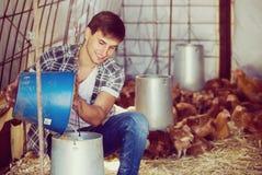 Secchio della tenuta dell'agricoltore con il foraggio del pollo Fotografie Stock Libere da Diritti
