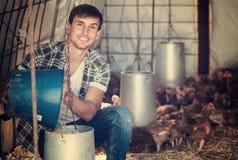 Secchio della tenuta dell'agricoltore del giovane in pollaio Immagine Stock Libera da Diritti