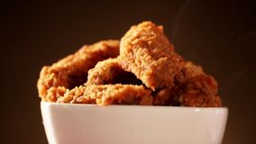 Secchio di rotazione in pieno del pollo fritto croccante del Kentucky con fumo su fondo marrone stock footage