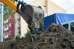 Secchio-escavatore del primo piano che funziona con la terra nera Fotografia Stock