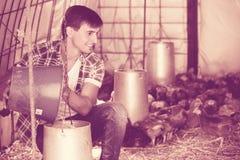 Secchio felice della tenuta dell'agricoltore del giovane Fotografia Stock