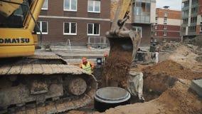 Secchio lento dell'escavatore di Panshot che scarica sabbia nella fossa della fogna al cantiere video d archivio