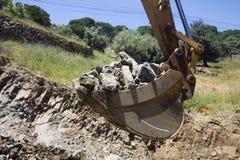 Secchio scavatore in pieno delle rocce Immagini Stock