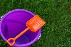 Secchio viola con la pala arancione Fotografie Stock