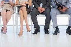 Sección baja de la entrevista de trabajo de la gente que espera para en oficina Imagenes de archivo