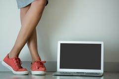 Sección baja de la lona que lleva de la mujer que se coloca al lado del ordenador portátil fotografía de archivo