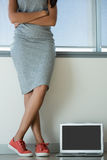 Sección baja de la lona que lleva de la mujer que se coloca al lado del ordenador portátil imagen de archivo