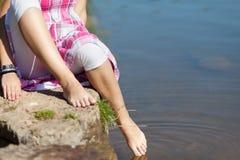 Sección baja de la muchacha que sumerge el pie en agua Imagen de archivo libre de regalías