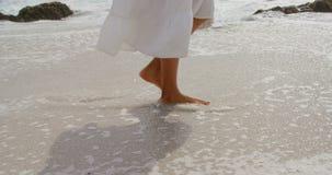 Sección baja de la mujer que camina descalzo en un día soleado en la playa 4k almacen de video