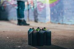 sección baja de la pintada en la noche, latas de la pintura del artista de la calle con la pintura del aerosol Fotografía de archivo libre de regalías