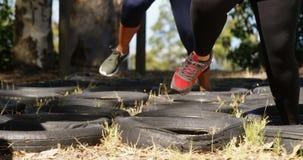 Sección baja de las mujeres que corren sobre los neumáticos durante carrera de obstáculos almacen de video