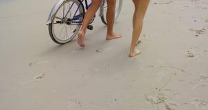 Sección baja de los pares caucásicos que caminan con la bicicleta en la playa 4k almacen de metraje de vídeo