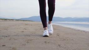 Sección baja de los pies de la mujer que caminan en la playa almacen de metraje de vídeo