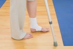 Sección baja de una mujer con la muleta y la pierna vendada Foto de archivo