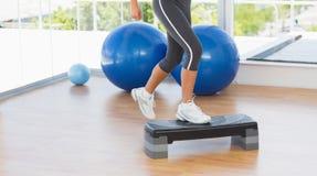 Sección baja de una mujer del ajuste que realiza ejercicio de los aeróbicos del paso Foto de archivo