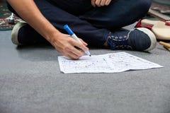Sección baja del batería Writing Notes While que se sienta en piso foto de archivo
