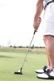 Sección baja del hombre de la edad adulta media que juega a golf contra el cielo claro imágenes de archivo libres de regalías