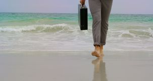 Sección baja del hombre de negocios que camina descalzo con la cartera en la playa 4k almacen de metraje de vídeo