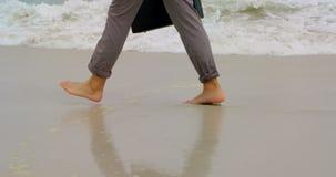 Sección baja del hombre de negocios que camina descalzo con la cartera en la playa 4k almacen de video
