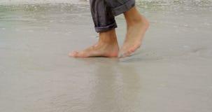 Sección baja del hombre de negocios que camina descalzo en la playa 4k metrajes