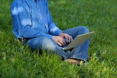 Sección baja del hombre de negocios Using Laptop While que se sienta en hierba Fotos de archivo libres de regalías