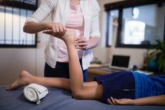 Sección baja del muchacho que recibe masaje del pie de terapeuta de sexo femenino joven imagen de archivo