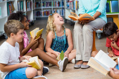 Sección baja del profesor con los libros de lectura de los niños imagenes de archivo