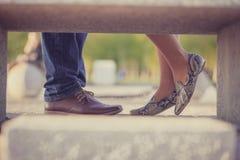 Sección baja, par cosechado de la imagen que se coloca en zapatos elegantes en un parque, cerca de uno a imágenes de archivo libres de regalías