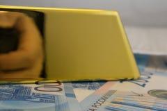 Sección de madera en la caja fuerte que desborda por completo del lingote de oro suizo 999 9 cuentas de ensayo y de dinero la ide imagen de archivo libre de regalías