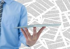Sección del hombre de negocios mediados de con la tableta contra el contexto del documento Fotografía de archivo libre de regalías