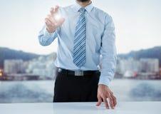 Sección del hombre de negocios mediados de en el escritorio con la llamarada contra horizonte borroso Imágenes de archivo libres de regalías