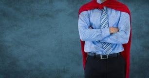 Sección del super héroe del hombre de negocios la mediados de con los brazos dobló contra fondo y la capa azules del grunge fotografía de archivo libre de regalías