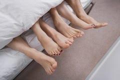 Sección baja de la mujer con dos hombres en cama Foto de archivo libre de regalías
